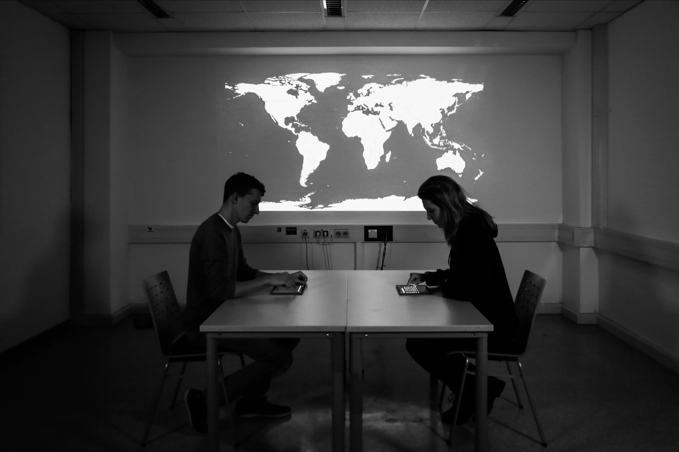 Two people sitting across from each other at a table in a dark room. On the table is a tablet in front of each person. A large world map is projected on the wall next to the table.
