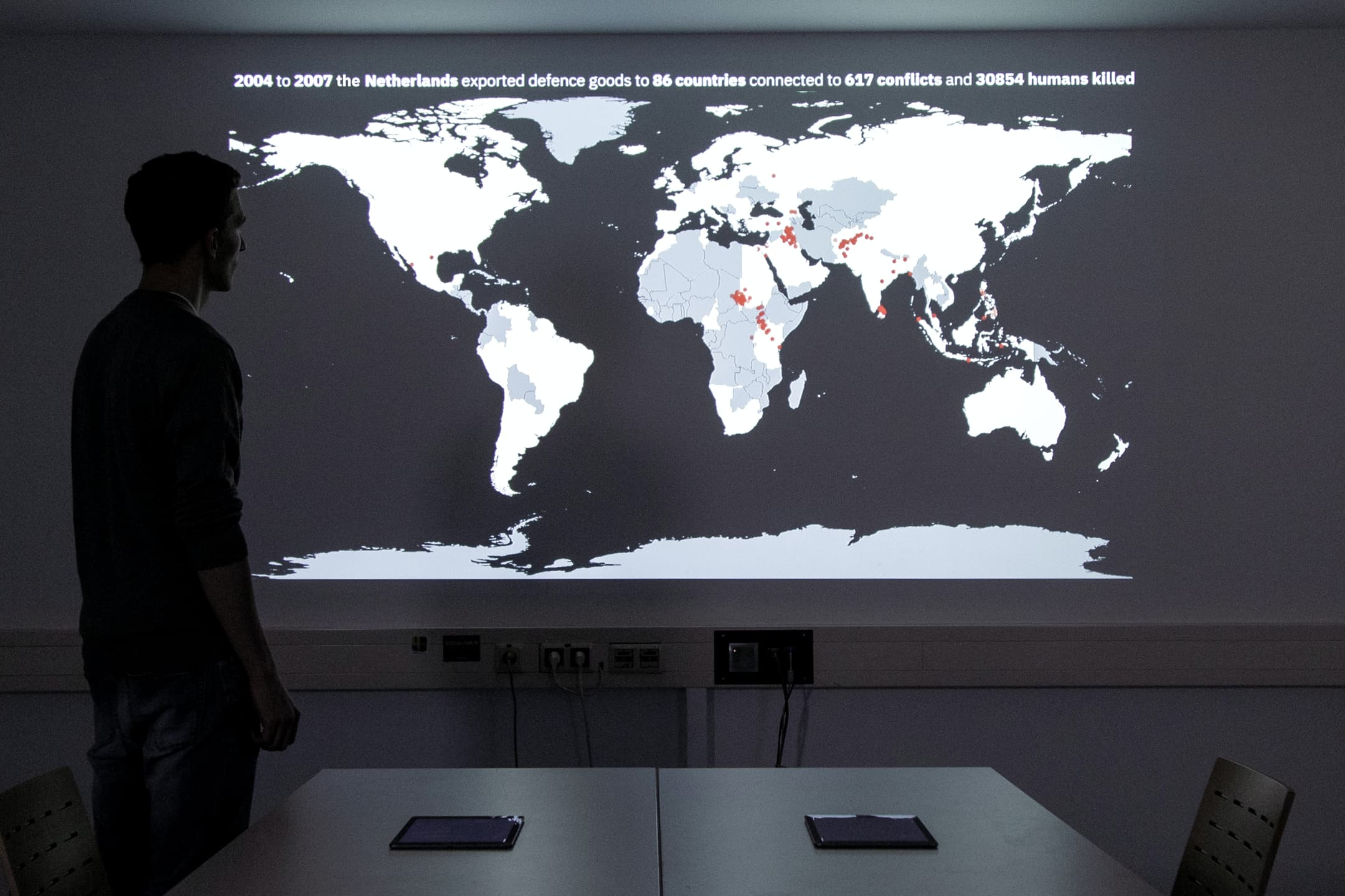 """Person standing in front of a projection of a world map. The text above the map reads: """"2004 to 2007 the Netherlands exported defence goods to 86 countries connected to 617 conflicts and 30854 humans killed�"""